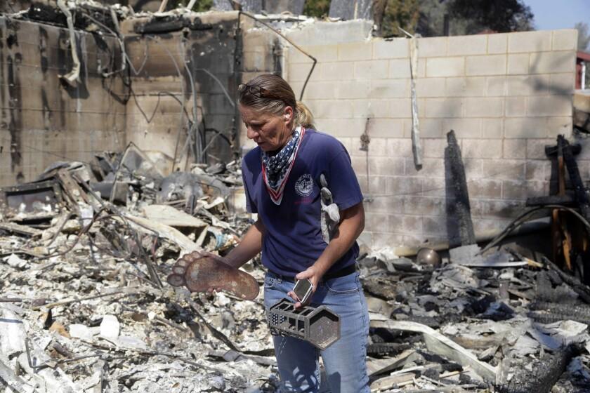 Karrie H. Andrews recupera objetos salvados de entre las ruinas de su casa, el 26 de julio de 2016, tras un incendio que arrasó Santa Clarita, California. (AP Foto/Nick Ut)