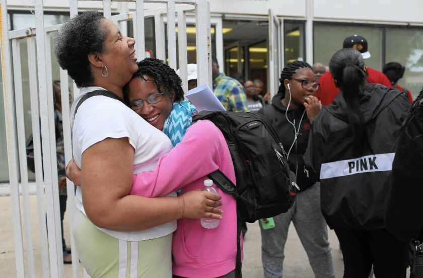 Cathalyn Washington, 16, hugs her mother, Yolanda Washington, on June 20, 2015, before boarding a bus with other Chicago students to O'Hare International Airport for their flight to China for two-week cross-cultural academic visit, offered through the Chicago Urban League.