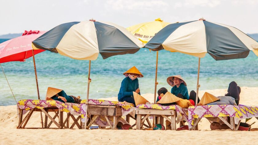 Beach masseuses resting under umbrellas