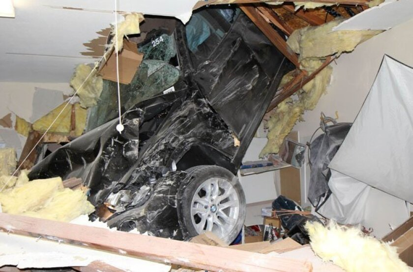 A BMW slammed through the roof of the garage of an Escondido home early Wednesday morning. — Photo by George Strother
