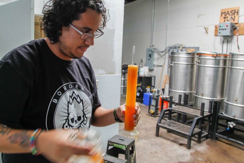 Head brewer Joaquin Basauri tests the gravity of a batch of beer in the brewery at Border X Brewing Co. in Barrio Logan.