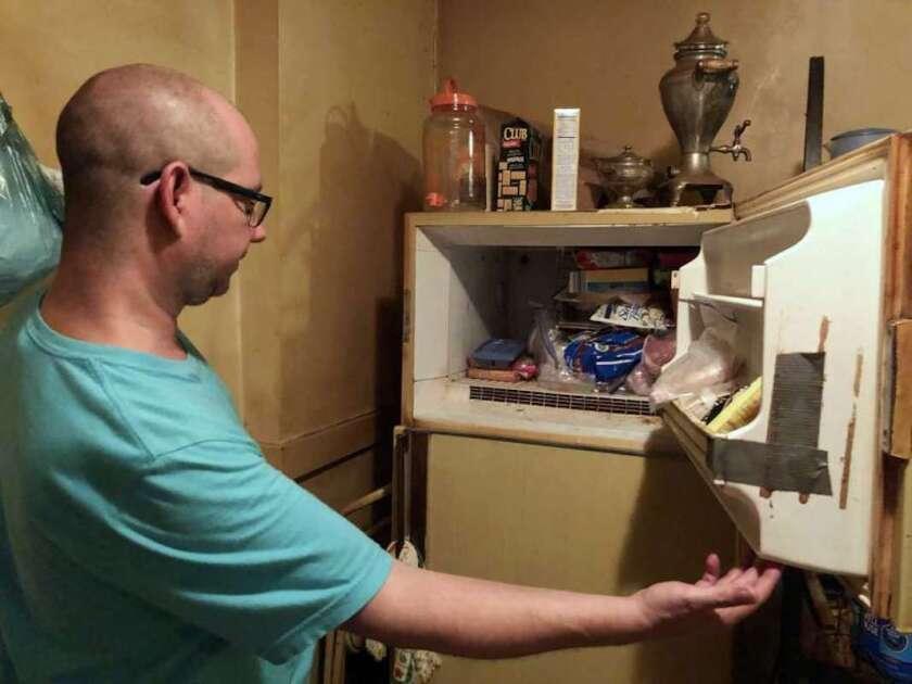 Adam Smith se asoma al congelador de su madre en St. Louis, donde dice que encontró los restos de un bebé en una caja y que ella mantuvo allí durante más de 40 años. La madre falleció el 21 de julio, a la edad de 68 años, por cáncer de pulmón.
