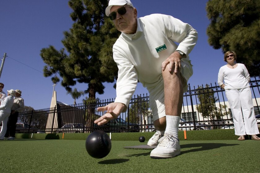 At the Coronado Lawn Bowling club Friday, Allan Lamotte showed Amy Cahill the proper way to release the bowl. Nelvin C. Cepeda / Union-Tribune