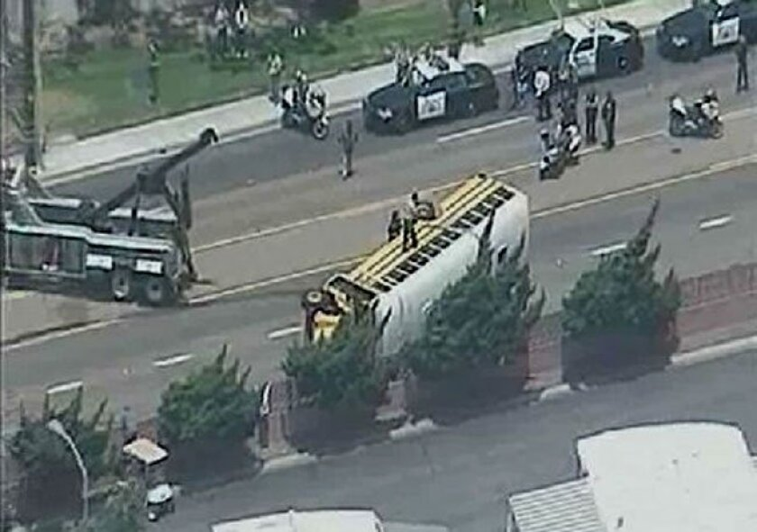 A California Highway Patrol officer stands atop an overturned schoolbus in Oceanside Wednesday, June 9, 2010 in this screen grab from Sky10 video.