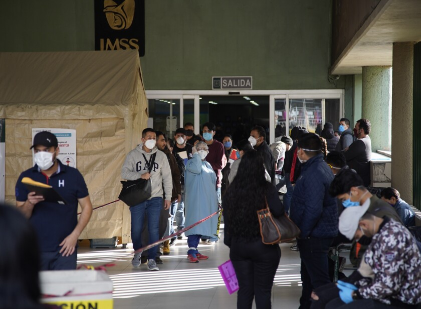 People wait outside IMSS Clinica 20 in Tijuana.