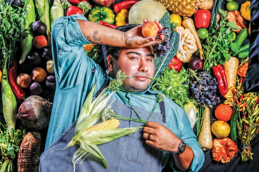 A chef poses playfully on a backdrop of vegetables.