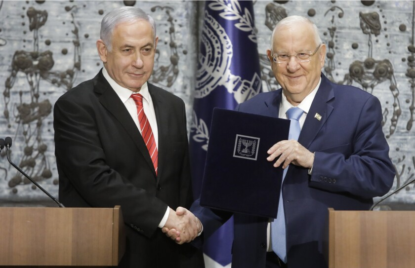 FILE - In this Wednesday, Sept. 25, 2109 file photo, Israeli President Reuven Rivlin, right, shakes hands with Israeli Prime Minister Benjamin Netanyahu in Jerusalem. For the sixth time in his lengthy political career, Netanyahu has been tasked by Israel's president to form a new government. This time it's no mere formality, but rather a daunting endeavor that looks like mission impossible. (AP Photo/Sebastian Scheiner, File)