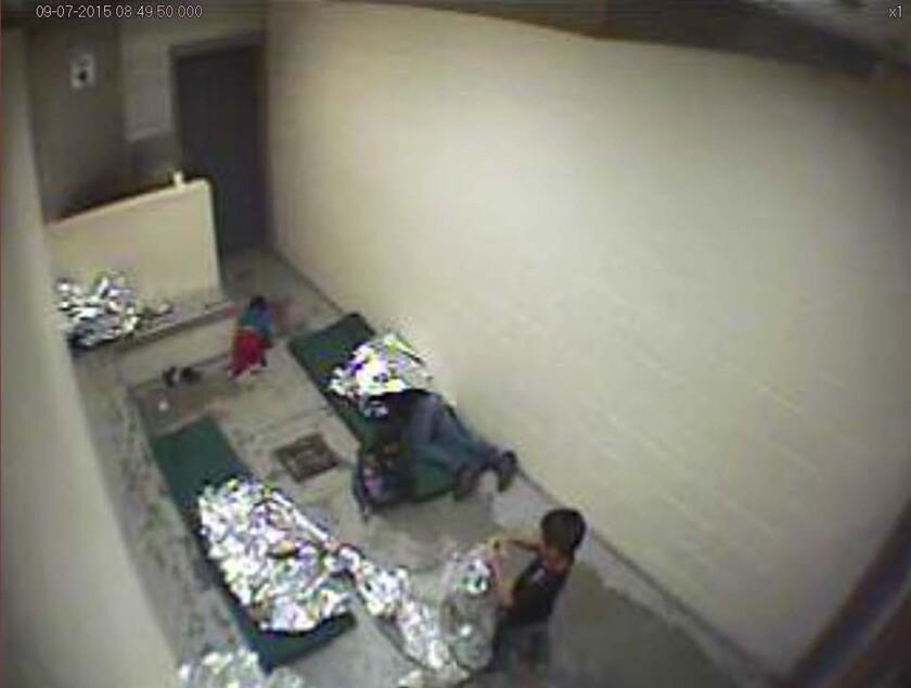Imagen de septiembre de 2015 tomada del video de una cámara de vigilancia de la Patrulla Fronteriza de Estados Unidos muestra un niño gateando en el piso de concreto cerca del área del baño de una celda de detención, así como a una mujer y un niño, en la estación de la Oficina de Aduanas y Protección Fronteriza de Estados Unidos en Douglas, Arizona, el miércoles 17 de agosto de 2016. (Patrulla Fronteriza de Estados Unidos vía AP)