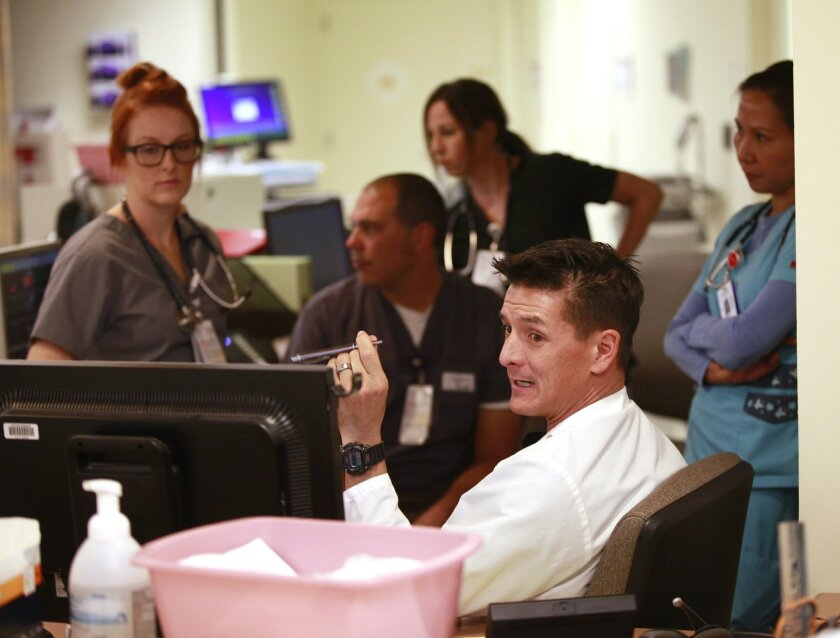 Dr. Christopher Hohas huddles with an emergency department team at Sharp Memorial Hospital in Kearney Mesa on Oct. 28. Sharp, and several other local health providers, have seen increases in emergency room traffic since new insurance requirements  put in place by the Affordable Care Act started on
