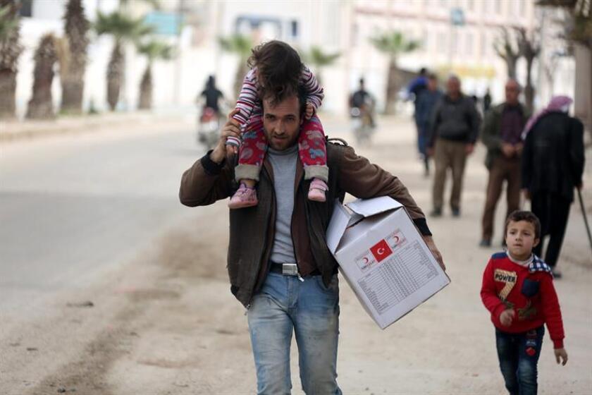 Varias personas transportan sus pertenencias por una calle de Afrín, Siria. EFE