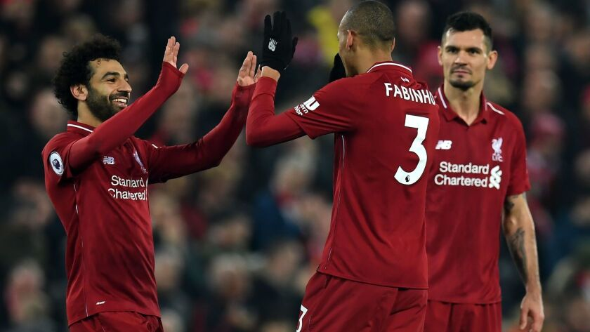 Liverpool's midfielder Fabinho, center, celebrates with midfielder Mohamed Salah, left, and defender Dejan Lovren after he scores their fourth goal during the English Premier League match between Liverpool and Newcastle United on Wednesday.