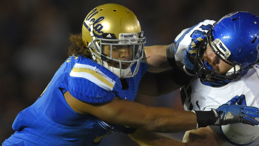 UCLA linebacker Eric Kendricks, left, battles with Memphis tight end Alan Cross during the second half of the Bruins' 42-35 win in September.