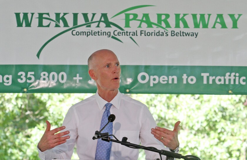 Florida Governor Rick Scott, shown speaking in 2013, is heading to Chicago to try to recruit Illinois businesses to come to the Sunshine State.