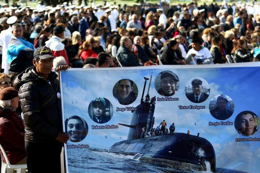 A man holds a sign with the pictures of some of the crew members of the Ara San Juan during a tribute a year after the disappearance of the Argentinian submarine ARA San Juan, in Mar del Plata, Argentina, Nov. 15, 2018. EPA-EFE/FILE/Eduardo Lopez