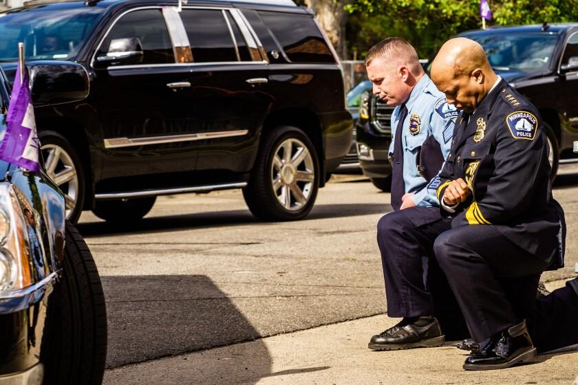 Minneapolis Police Chief Medaria Arradondo (R) kneels as the remains of George Floyd are taken to a memorial service.