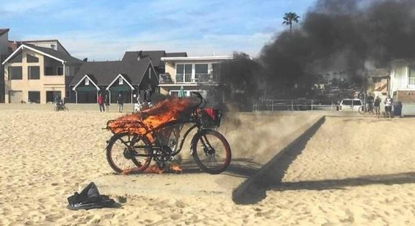 An electric bike burns on the beach on the Balboa Peninsula in Newport Beach on Sunday. No one was injured.