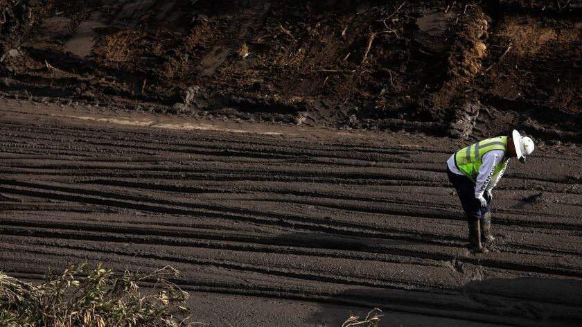 A worker takes a breather from directing a bulldozer driver who clears mud from the 101 freeway in Montecito on January 16, 2018.