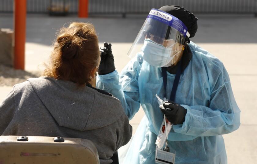 A nurse uses a nasal swab to conduct a coronavirus test
