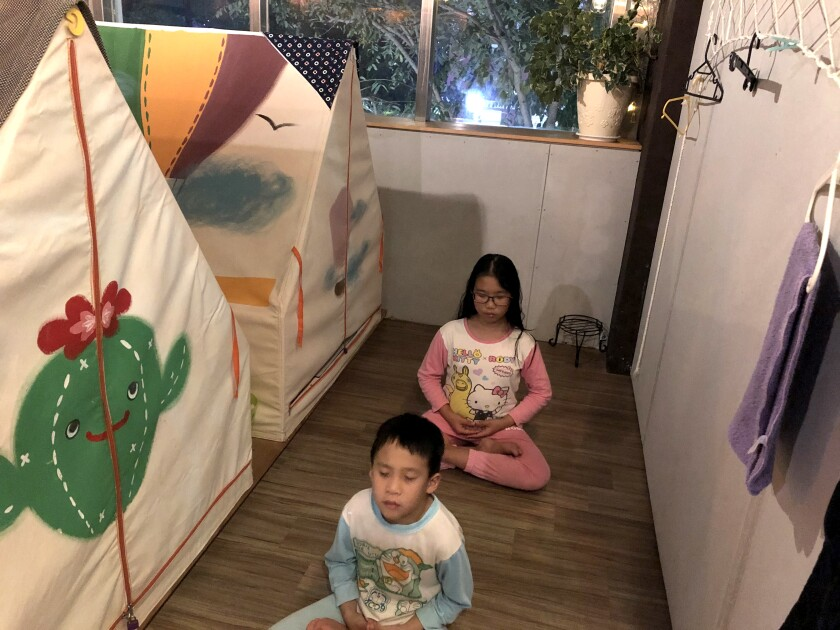 Yu Chung-chieh, 7, foreground, and Yu Shan-chen, 12, say prayers before bedtime at Ponponwu, an indoor campground in Taiwan.