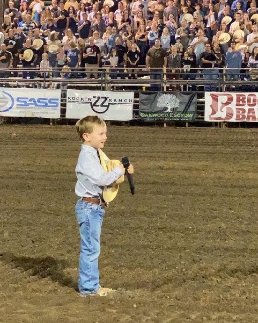 Luke Duba, 4, son of Kayla and Dusty Duba, leads the Ramona Rodeo crowd in reciting the Pledge of Allegiance.