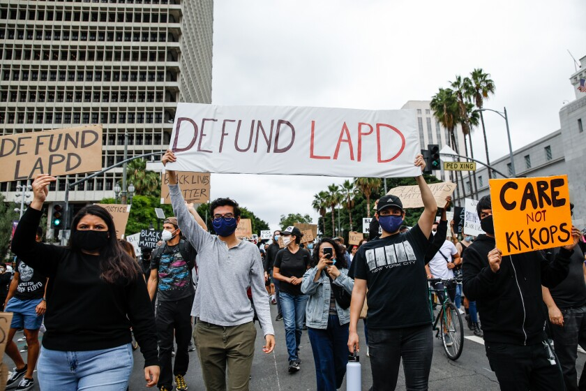 "Signs, including ""Defund LAPD,"" are held high during a protest in support of Black Lives Matter on June 5 in downtown L.A."