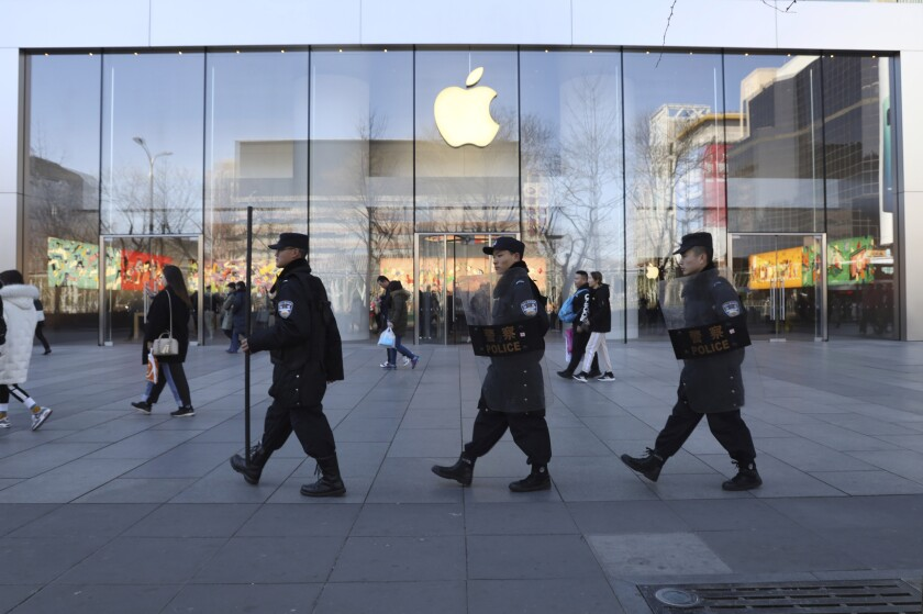 """FILE - In this March 6, 2019, file photo, Chinese security guards march past an Apple store in Beijing, China. Apple is temporarily closing its 42 stores in mainland China, one of its largest markets, as a new virus spreads rapidly and the death toll there rose to 259 on Saturday, Feb. 1, 2020. The iPhone maker said in a statement it was closing stores, corporate offices and contact centers in China until Feb. 9 """"out of an abundance of caution and based on the latest advice from leading health experts."""" (AP Photo/Ng Han Guan, File)"""