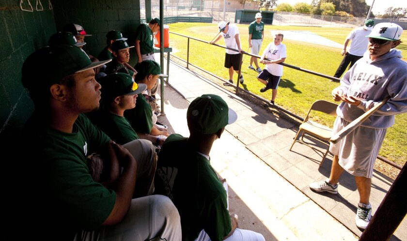 Helix Highlanders coach Cole Holland, right, speaks to players before warm-up and drills. On cover, third baseman Austin Hopwood fields ground balls during a recent team practice. NELVIN C. CEPEDA • U-T