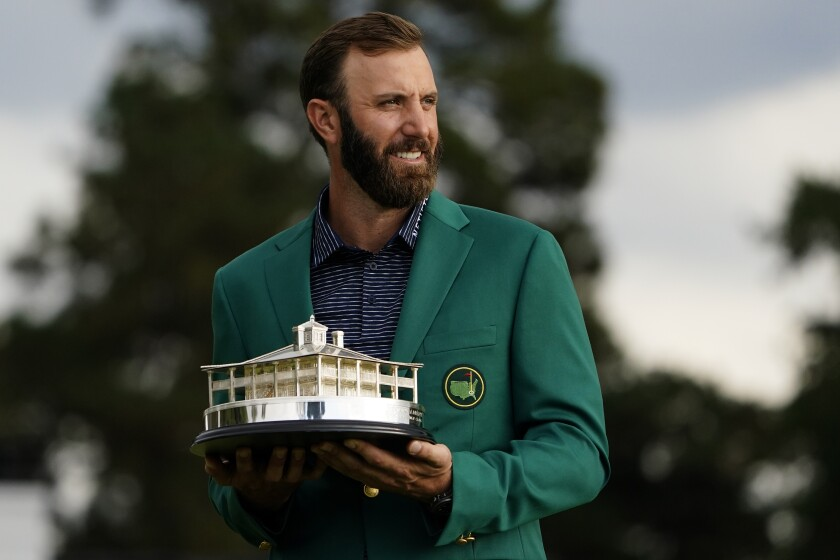 Masters golf champion Dustin Johnson holds the tournament trophy after his victory Sunday.