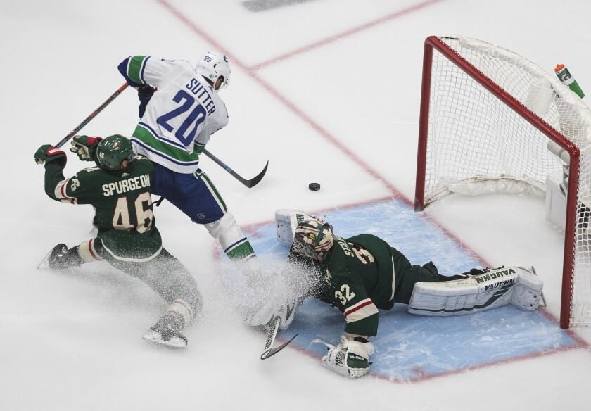 Minnesota Wild goalie Alex Stalock (32) makes the save on Vancouver Canucks' Brandon Sutter (20) as Wild's Jared Spurgeon (46) defends during the third period of an NHL hockey qualifying round game, Friday, Aug. 7, 2020, in Edmonton, Alberta. (Jason Franson/The Canadian Press via AP)