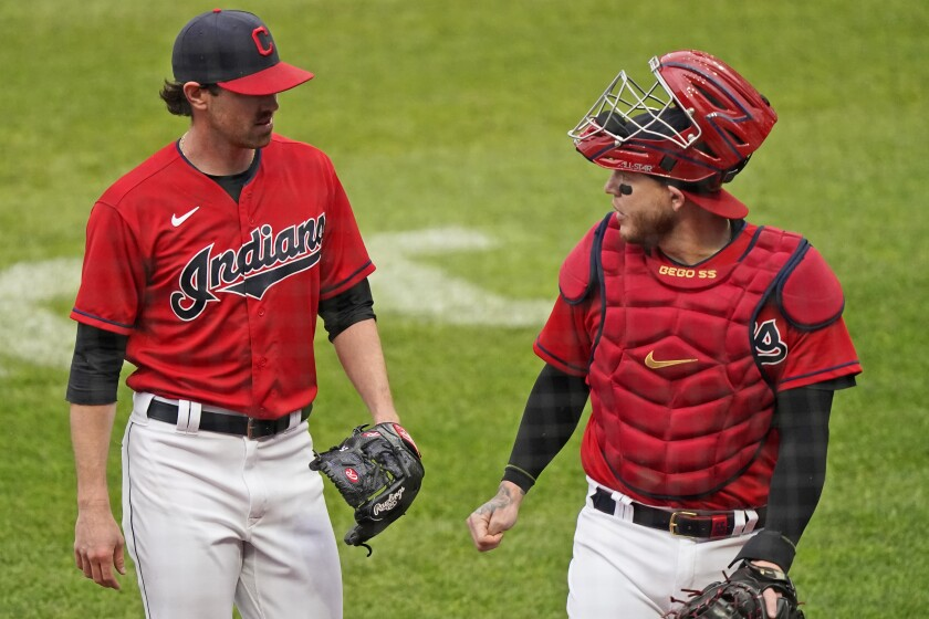 Cleveland Indians starting pitcher Shane Bieber, left, and catcher Roberto Perez walk to the dugout in the first inning of a baseball game against the New York Yankees, Saturday, April 24, 2021, in Cleveland. (AP Photo/Tony Dejak)