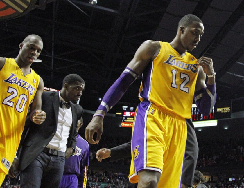 Lakers Jodie Meeks, left, and Dwight Howard exit the court after a 116-106 loss to the Trail Blazers in Portland.
