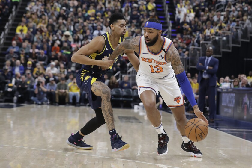 New York Knicks' Marcus Morris Sr. (13) is defended by Indiana Pacers' Jeremy Lamb (26) during the first half of an NBA basketball game, Saturday, Feb. 1, 2020, in Indianapolis. (AP Photo/Darron Cummings)