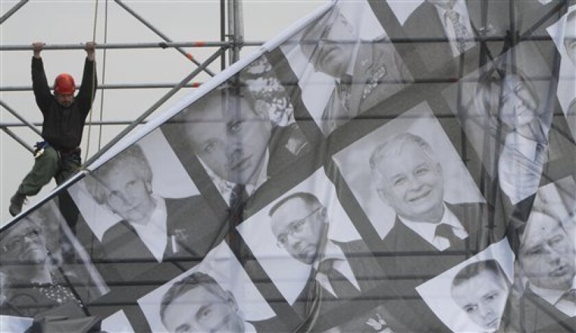 Workers attach a giant poster depicting the photos of the killed people and Pilsudski square on Friday, April 16, 2010 in Warsaw, Poland, where a commemoration service for all victims is going to be held on Saturday.  Polish President Lech Kaczynski who was killed in a plane crash in Russia is goin