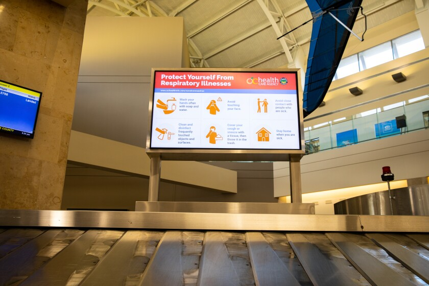 """A screen with info on how to """"Protect Yourself From Respiratory Illnesses"""" above an empty baggage carousel."""