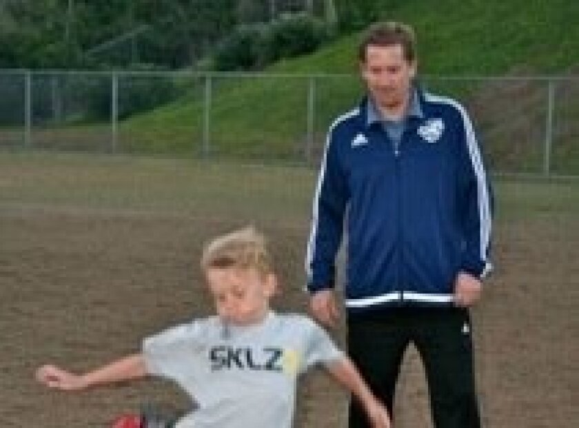 BU9 Coach Brett Mills works on shooting skills with player William Robinson.