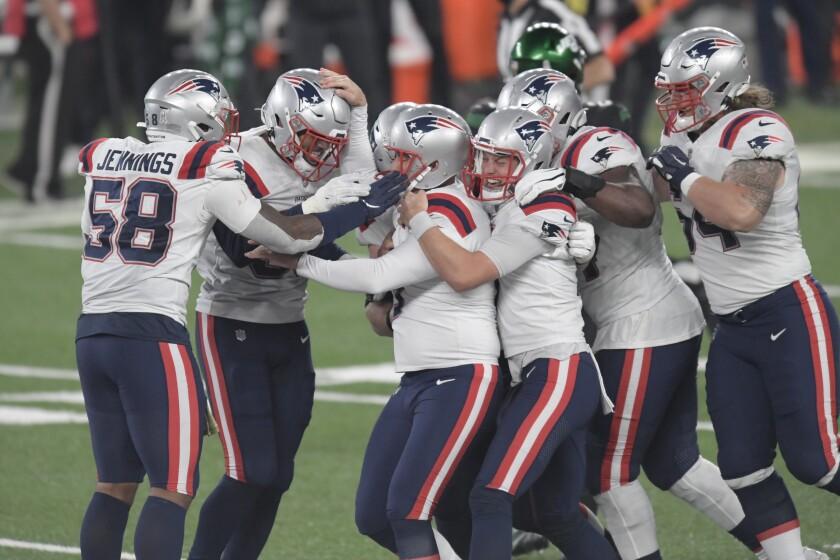 New England Patriots kicker Nick Folk celebrates with teammates after kicking the winning field goal.