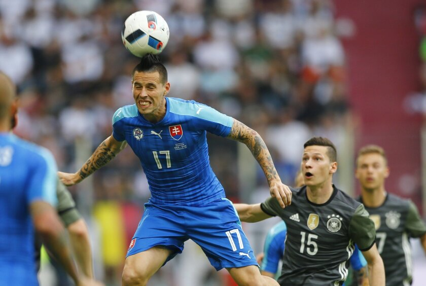 FILE - In this Sunday, May 29, 2016 file photo, Slovakia's Marek Hamsik, left, and Germany's Julian Draxler challenge for the ball during a friendly soccer match between Germany and Slovakia in Augsburg, Germany. (AP Photo/Matthias Schrader, File)