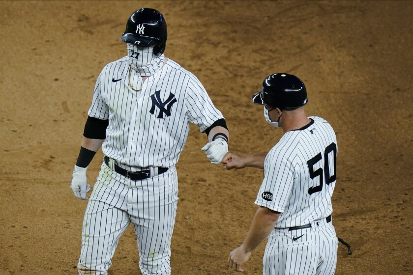 New York Yankees' Clint Frazier (77) fist bumps first base coach Reggie Willits (50) after hitting a two-run single during the seventh inning of a baseball game Saturday, Aug. 15, 2020, in New York. (AP Photo/Frank Franklin II)