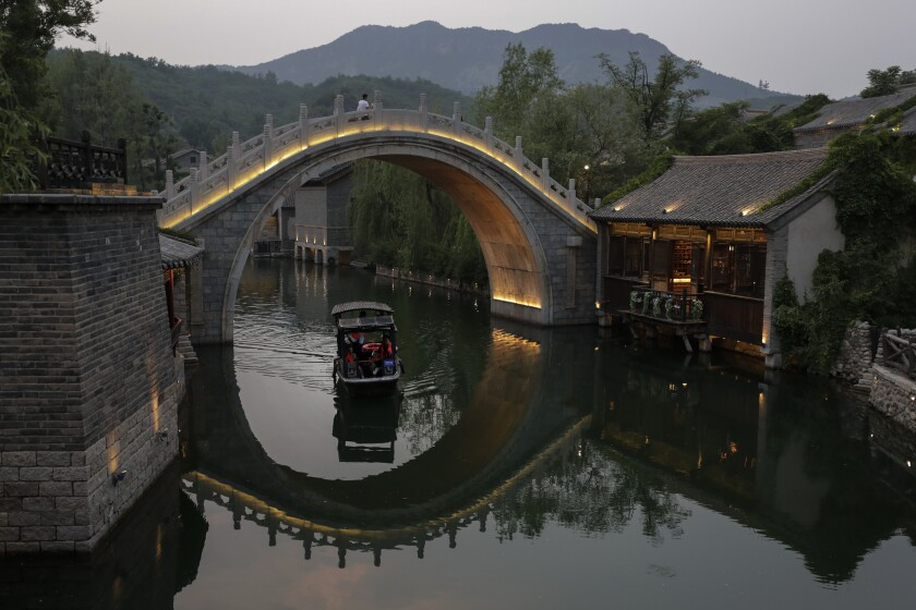 Visitors ride a boat at the ancient village in Gubei Water Town, a popular tourist spot in Beijing, Tuesday, June 9, 2020. With declining virus case numbers, many tourism places and businesses in the capital city are gradually open to visitors and residents go about their usual activities. (AP Photo/Andy Wong)