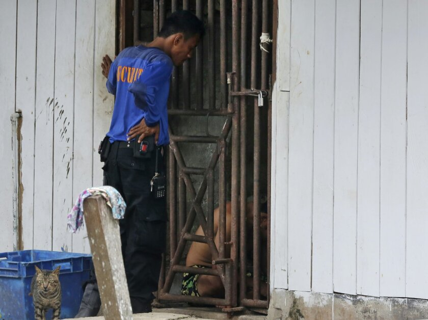 FILE - In this Nov. 2014, file photo, a security guard talks to detainees inside a cell at the compound of a fishing company in Benjina, Indonesia. The imprisoned men were considered slaves who might run away. They said they lived on a few bites of rice and curry a day in a space barely big enough