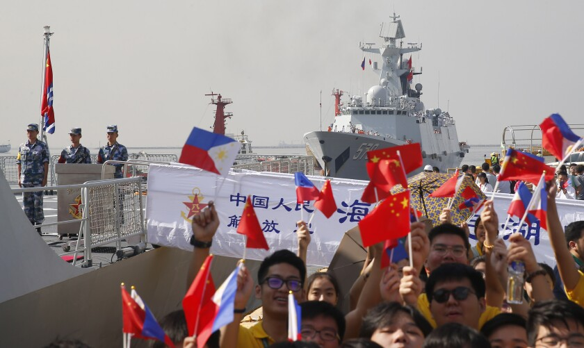 Students wave Philippine and Chinese flags during a visit by Handan, a Chinese guided missile frigate, to the port of Manila in January 2019.