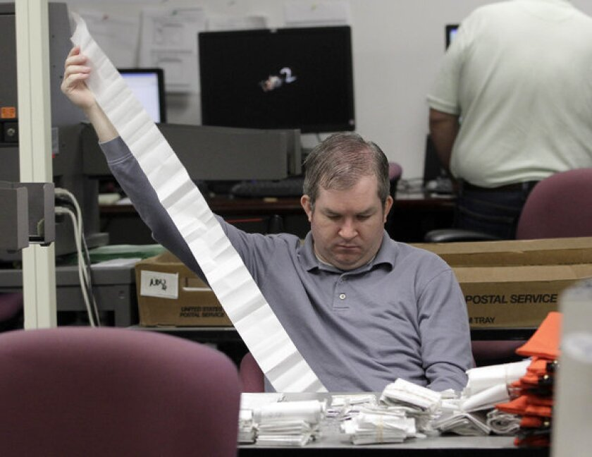 A Miami-Dade Elections Department employee tallies absentee ballot reports in Doral, Fla.