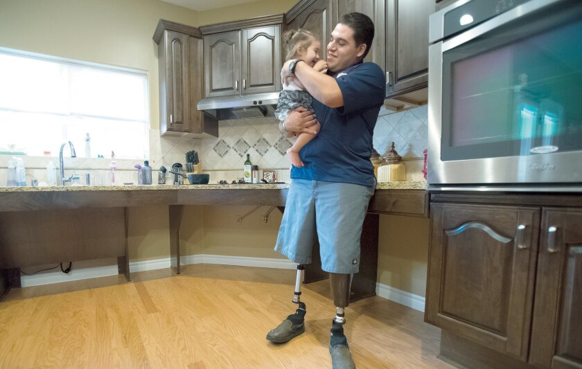 Sgt. Julian Torres and his 19-month-old daughter, Analicia, in the kitchen of their new home.