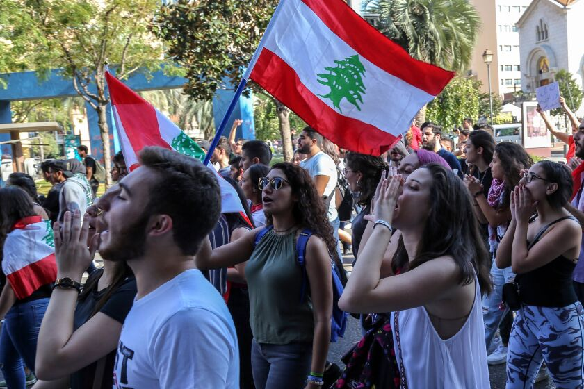 Lebanese students from various universities shout slogans during ongoing anti-government protests as they march from Lebanese University toward Riad Solh Square in Beirut.