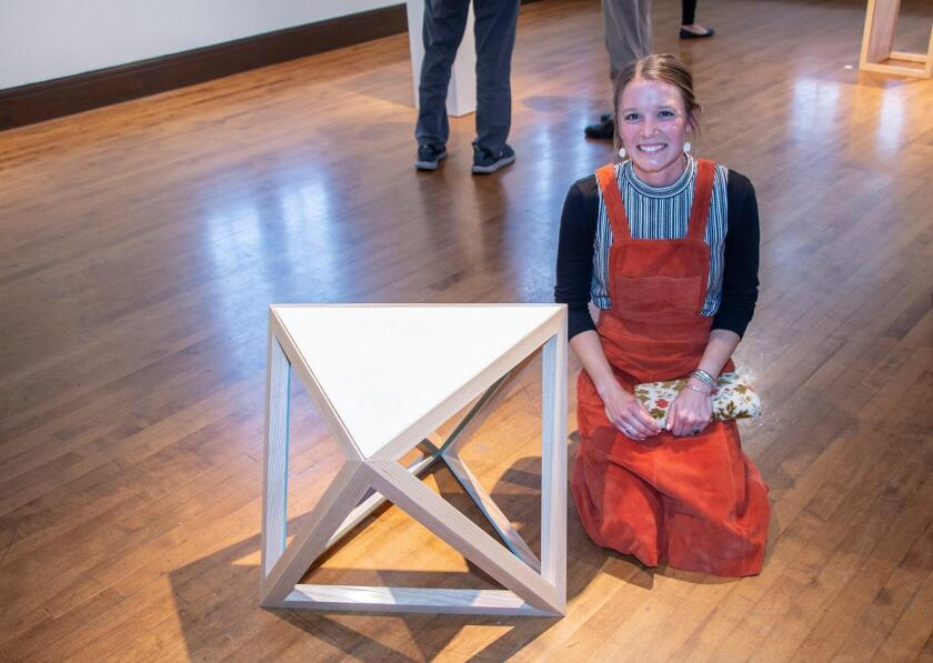 Erin Dace Behling with her triangular triangular wood and concrete side table
