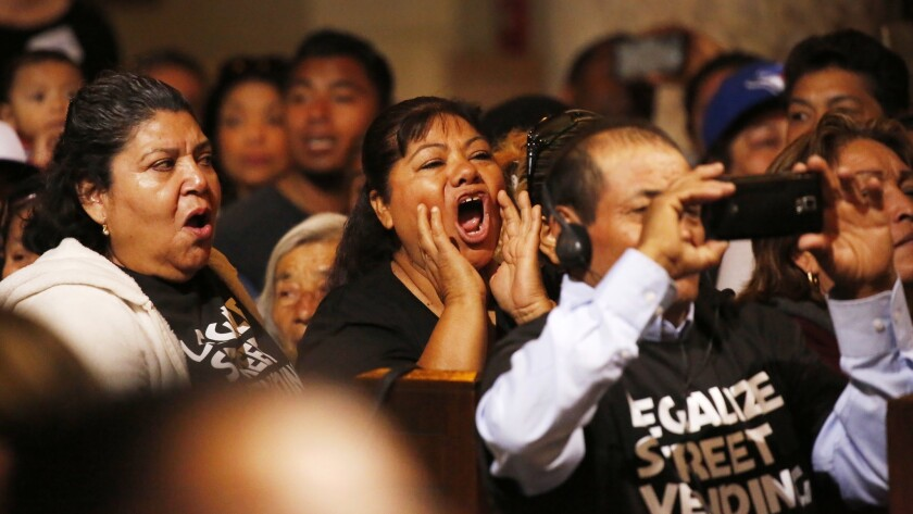 Street vendors in the audience call out as the L.A. City Council discusses the vote to pass an ordinance on street vending in which brick-and-mortar businesses could offer input to try to stop vendors from setting up shop on nearby sidewalks.