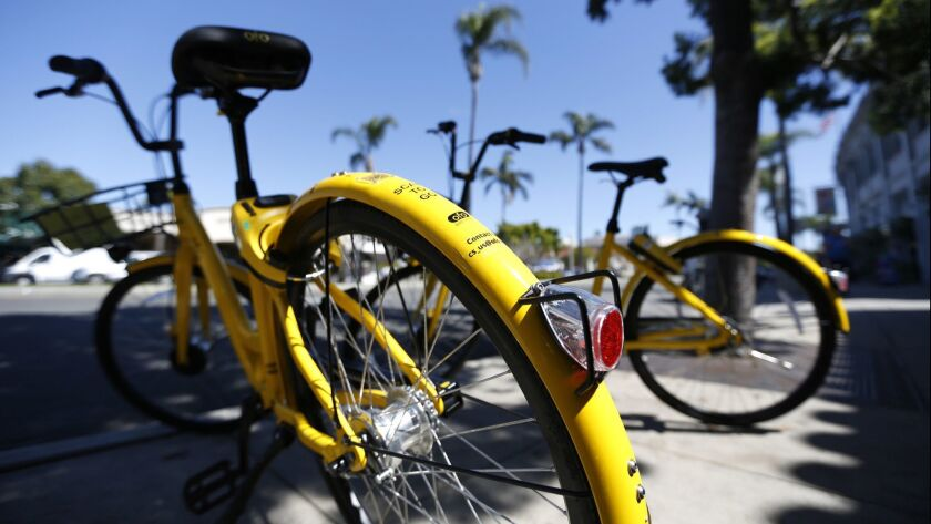 Two ofo dockless bikes are parked along Orange Avenue in Coronado on March 19, 2018. The city of Coronado plans to impound the bicycles.