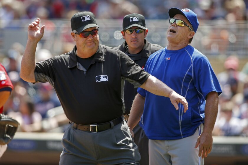 Umpire Joe West, left,ejects Toronto Blue Jays manager John Gibbons, right, as umpire Mark Ripperger, center, watches in the game with the Minnesota Twins in the fifth inning of a baseball game Sunday, May 22, 2016, in Minneapolis. (AP Photo/Bruce Kluckhohn)