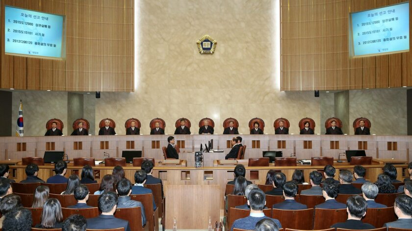 South Korean Supreme Court Chief Justice Yang Sung-tae, center in the background, sits with other justices before a judgment at the Supreme Court in Seoul, South Korea, Friday, Feb. 19, 2016. South Korea's top court has upheld a death penalty for a soldier convicted of killing five comrades in shoo