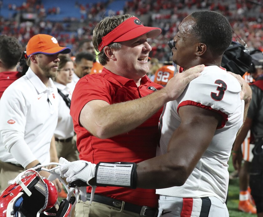 Georgia coach Kirby Smart and tailback Zamir White celebrate the team's win over Clemson in an NCAA college football game Saturday, Sept. 4, 2021, in Charlotte, N.C. (Curtis Compton/Atlanta Journal-Constitution via AP)
